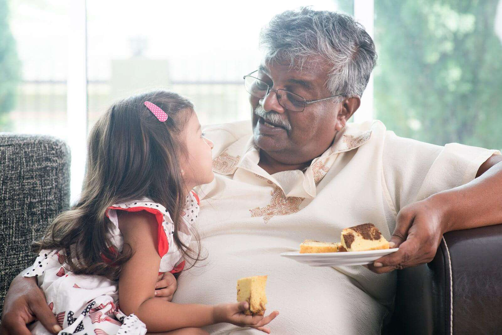 A grandfather eating with his grand daughter